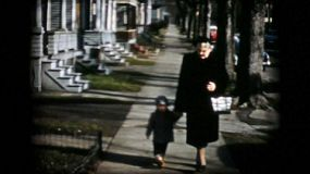 A proud Grandmother walks down the sidewalk in the Fall with her two grandsons in 1956.