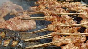 Chicken on a stick, pork and fish grilling at a street side food stall in Bangkok, Thailand.