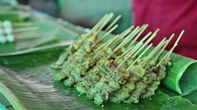 A street vendor lays out grilled pork on a stick, ready to sell at their street stall in Bangkok, Thailand.