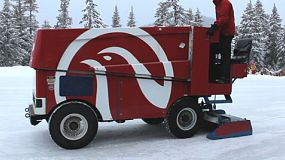 A zamboni ice cleaning machine carefully cleans the ice on a frozen skating rink on Grouse Mountain in Vancouver, BC, Canada.
