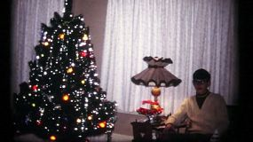 A handsome young teenage boy sits beside the beautifully decorated Christmas tree just waiting for Christmas morning in 1961.
