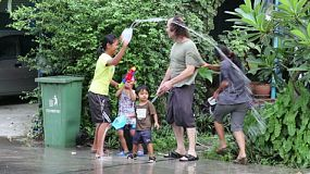 Asian people playing with water during the Songran New Year's festival in Thailand.