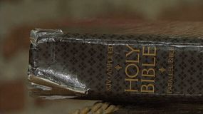 The camera begins with the reflection of the Holy Bible on the coffee table and then tilts up to the actual book.