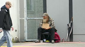 VANCOUVER, BC, OCTOBER 2015: An old homeless man living on the streets chuckles at a man passing by on the streets of Vancouver, BC.