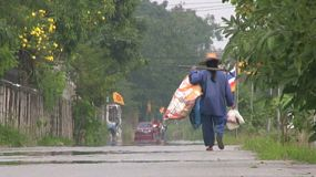 An homeless Asian man walks down the road on his way to look for some work in Bangkok, Thailand.