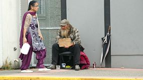 VANCOUVER, BC, OCTOBER 2015: An Indo Canadian woman carrying milk walks past a homeless man living on the streets of Vancouver, BC.