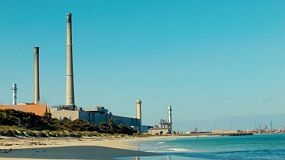 A beachside refinery plant with smokestacks and steam in an industrial area in Kwinana, Western Australia.