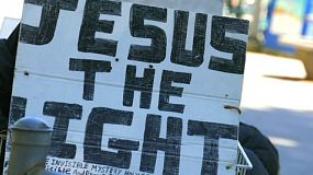 "A man with a ""Jesus The Light"" sign on the back of his bike in Vancouver, BC."