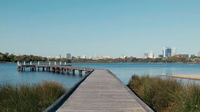 Looking down a jetty on the Swan River, with there Perth City skyline in the background.