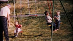 Kids having fun on a swing set being pushed by their Grandfather at the family picnic in 1964.
