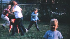A group of kid enjoy playing football and hanging out in the backyard in the summer of 1962.