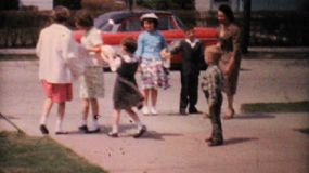 A bunch of well dressed kids have fun playing and dancing with their Aunt in the driveway in 1962.