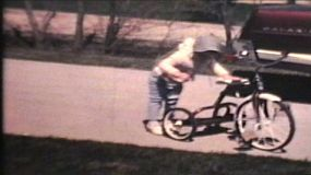 Three siblings ride tricycles and bikes in their drive way in front of some classic 60's cars on a crisp spring day.