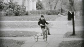 Kids riding old style bikes down the sidewalk in the summer of 1955.