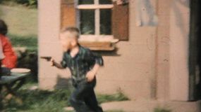 Kids play with toy guns as they run and chase each other during the big family reunion in the summer of 1959.