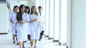A group of Asian lab technicians walk past the camera on their way to the laboratory.