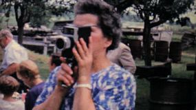 A lady films a large family picnic in the summer of 1962 with her 8mm moving camera.
