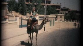 CAIRO, EGYPT, JUNE, 1957: A lady enjoys riding a camel to go and see the great pyramids of Egypt in the summer of 1957 just outside of Cairo.