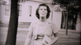 A pretty lady sticks her tongue out at the camera man as she walks back to her home in 1957.