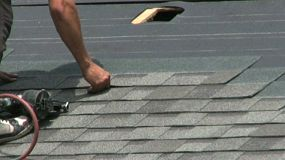 A man uses an automatic nail gun to lay shingles on a roof in the hot summer sun.
