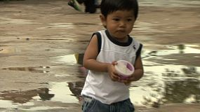 A cute little Asian boy enjoys walking through the park eating his snack, with his mother in Bangkok, Thailand.
