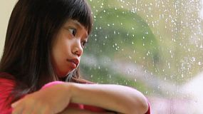 A sad seven year old Asian girl sits by a window watching the rain fall.