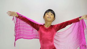 A cute little 7 year old Asian girl does a fun little creative dance.
