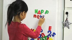 A cute little seven year old Asian girl uses colorful fridge magnet letters to spell Happy New Years.