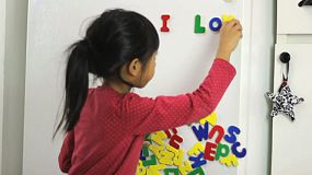 A cute little seven year old Asian girl uses colorful fridge magnet letters to spell I Love Dad on the fridge.