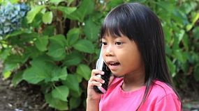 A cute little Asian girl talks to her grandparents on the phone.