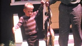 A little boy and his Grandpa proudly display their catch of fish while on holidays together in the summer of 1967.