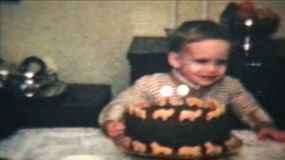 A cute little boy blows out the candles on his chocolate birthday cake. (Vintage 8mm film)