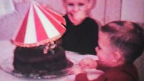 A cute little boy celebrates his 4th birthday with his brother and a chocolate cake in 1966.