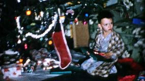A little boy opens presents on Christmas morning in 1956.