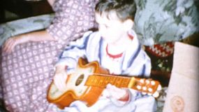 A little boy enjoys playing his brand new guitar on Christmas morning in 1956.