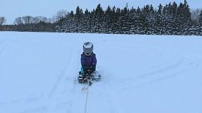 A cute little 10 year old girl enjoys being towed behind her Dad's snowmobile on her Snow Racer on a cold winter's day!