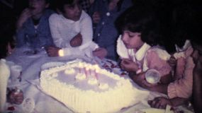 A cute little girl celebrates her sixth birthday in 1978 by blowing out the candles on her birthday cake in Caracas, Venezuela.