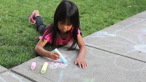 A cute little Asian girl enjoys creating some pretty sidewalk chalk art on a lovely summer day.