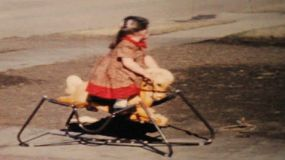 A cute little girl going crazy on her new rocking horse outside her home in the summer of 1964.