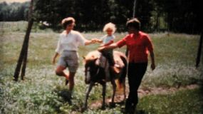A cute little girl goes for a pony ride on the family farm in the summer of 1962.
