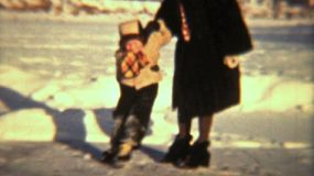 A cute little girl learns to skate on a frozen section of the river with the help of her patient mother.