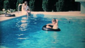 A cute little girl learns to swim in the new backyard swimming pool with the help of her older sister in 1967.