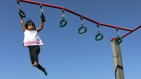 A cute little 3 year old Asian girl has fun on the rings at the playground during summer.