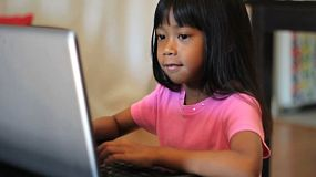 A cute little Asian girl has fun playing games on her parents lap top computer.