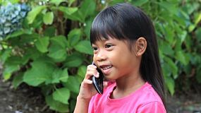 A cute little Asian girl talks to her daddy on her mommy's cell phone.
