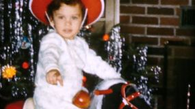 A cute little girl wearing a red cowboy hat enjoys riding her new rocking horse on Christmas Day in 1959.