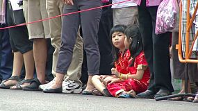 Two cute Asian girls wait patiently for the Chinese New Year parade to start.