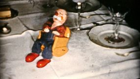 A cute little carving of an old man in a rocking chair blows smoke rings during the Christmas season in Cleveland, Ohio in 1956.