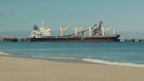 Looking across the beach at a bulk freighter ship docked at Kwinana, in Western Australia, ready for loading.