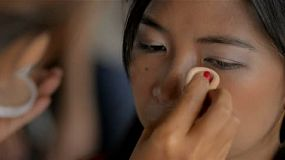A young beautiful Asian woman having makeup applied, the makeup artist is applying foundation with a sponge.
